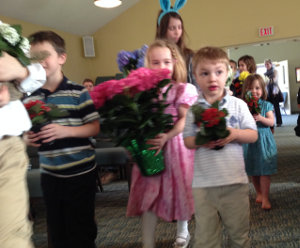 Children carrying flowers down the aisle of a sanctuary